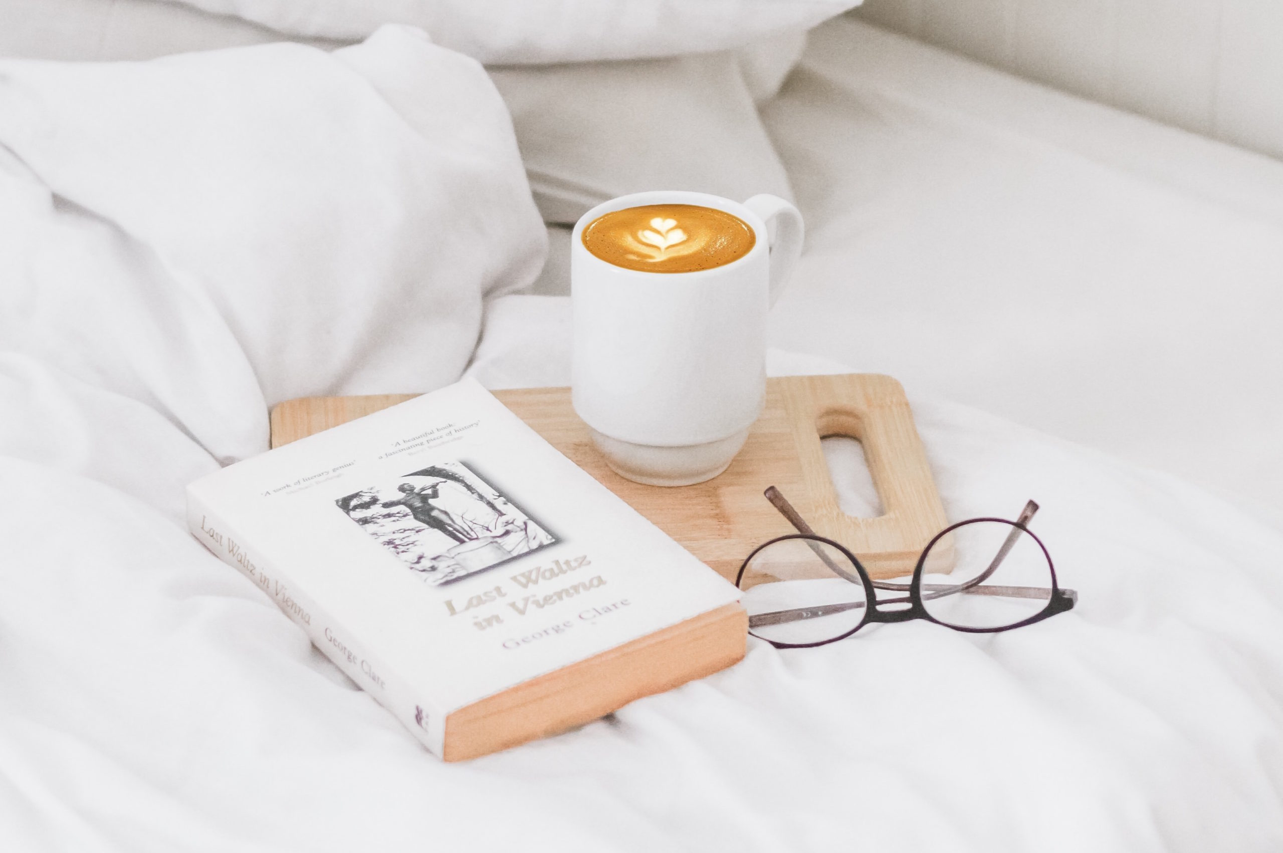Book, mug and reading glasses on a bed
